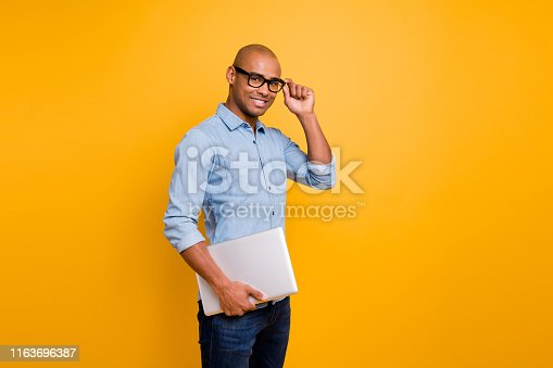 1163696387 istock photo Photo of dark skin guy notebook hands classroom young school teacher wear specs jeans denim shirt isolated bright yellow background 1163696387
