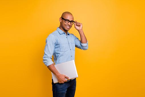 istock Photo of dark skin guy notebook hands classroom young school teacher wear specs jeans denim shirt isolated bright yellow background 1163696387