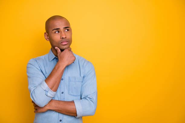 photo of dark skin macho interested look up empty space hand touch chin wear jeans denim shirt isolated bright yellow background - cynic stock pictures, royalty-free photos & images