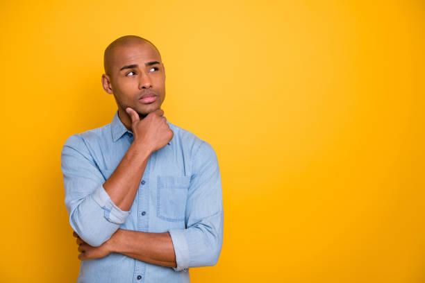 foto van donkere huid macho geïnteresseerd opzoeken lege ruimte hand touch chin wear jeans denim overhemd geïsoleerd fel gele achtergrond - achterdocht stockfoto's en -beelden