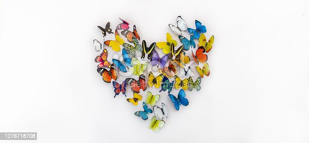 Photo of decorative flying butterflies pattern in heart shape isolated on white background with copy space. Spring summer season flat lay and top view concept banner