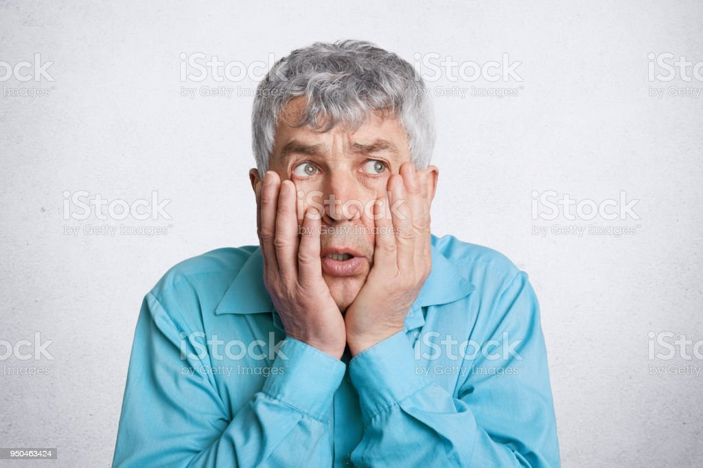 Photo of discontent frustrated grey haired male, keeps hands on cheeks, looks desperately somewhere, wears formal blue shirt, isolated over white concrete wall. People, problems and age concept stock photo