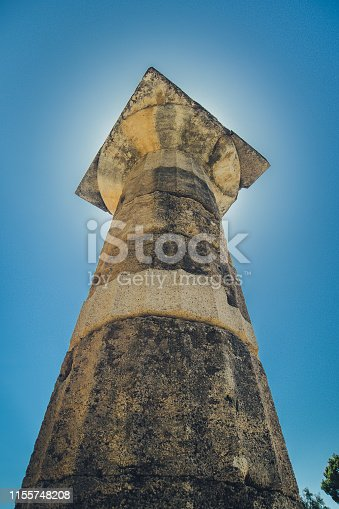 A vertical photo of Doric order column or pillar, photo taken on the ancient archeological site of Olympia, Greece, on a sunny day with sun shining directly behind the column