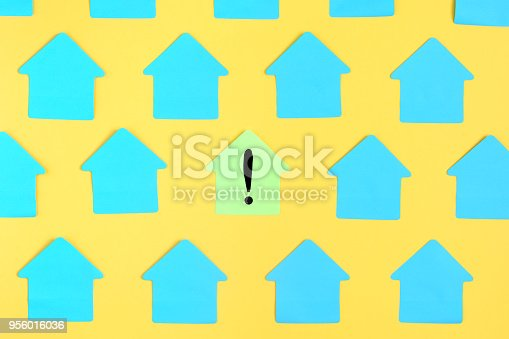 Photo of empty turquoise stickers on a yellow background. In the center there is a yellow sticker with an exclamation point. Bright background with the top, mock up.