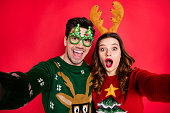 istock Photo of excited lady and guy chilling at newyear costume party making selfies wear funky pullovers with ugly ornaments isolated red color background 1175471446