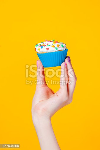 istock photo of female hand holding cupcake on the wonderful yellow background 677634660