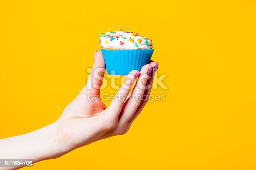 istock photo of female hand holding cupcake on the wonderful yellow background 677634706