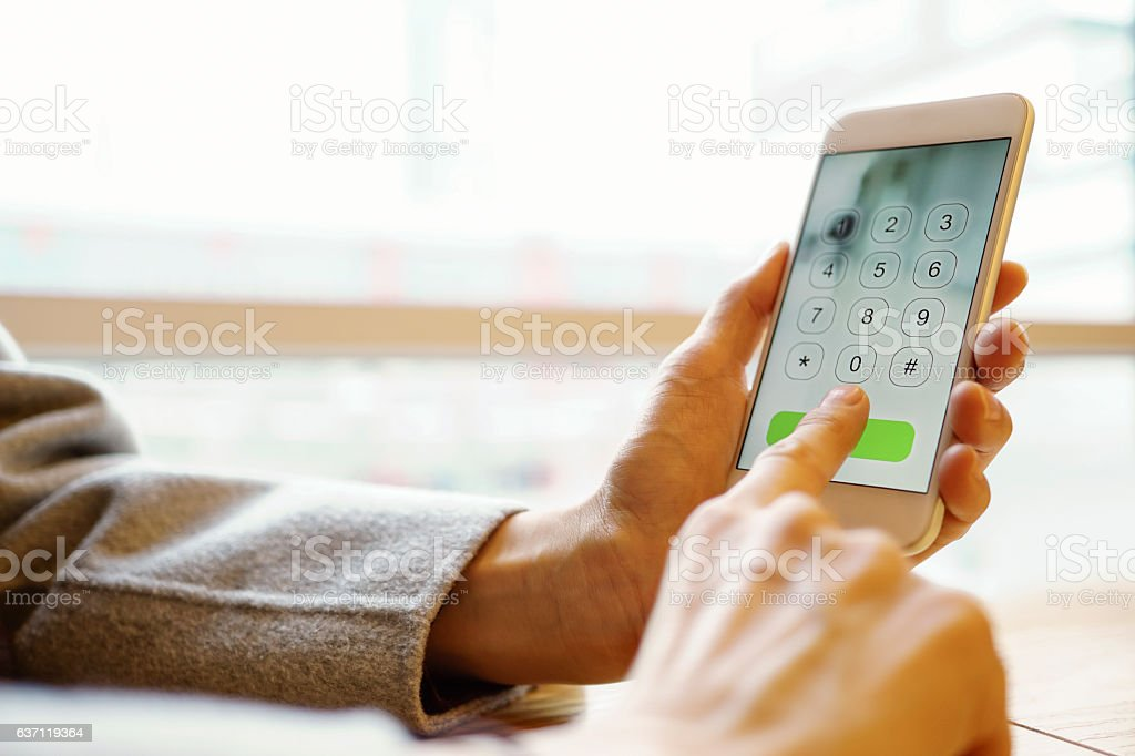 photo of female hands dialing a smartphone stock photo