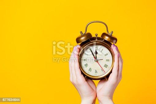 istock photo of female hands holding alarm clock on the wonderful yellow background 677634644