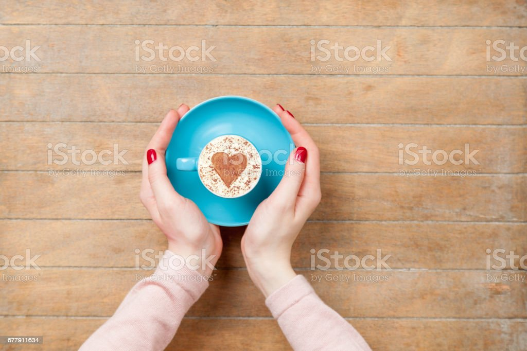 photo of female hands holding cup of coffee on the wonderful brown wooden background royalty-free stock photo