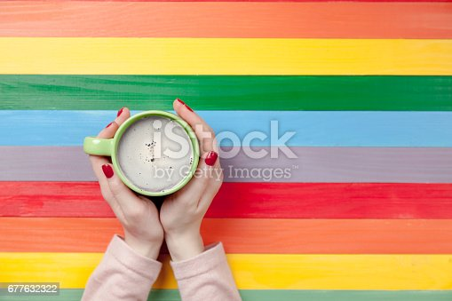 172214590 istock photo photo of female hands holding cup of coffee on the wonderful colorful background in pop art style 677632322