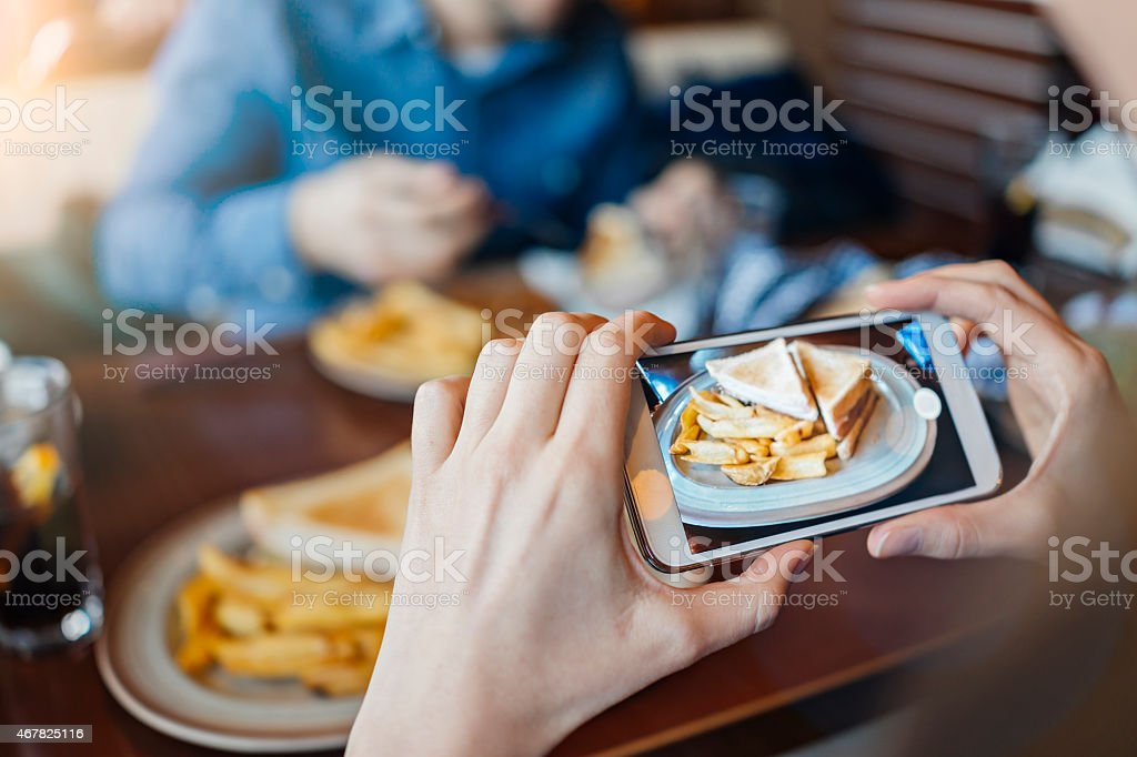 Photo of female hands using smartphone to photograph her lunch stock photo