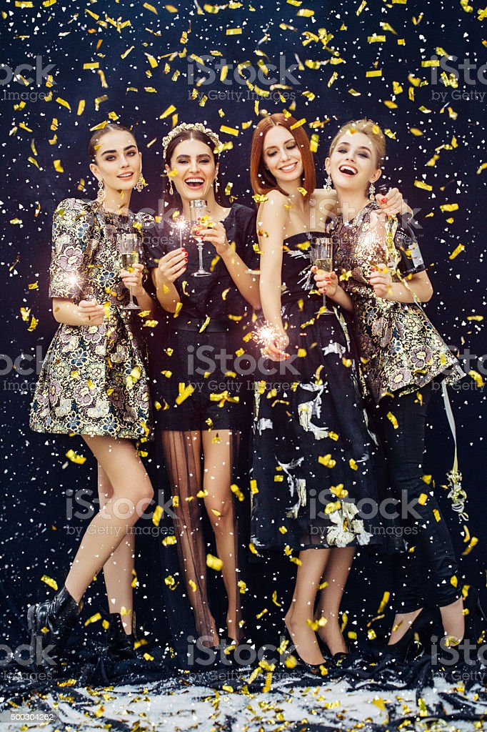 Photo of four laughing girls strewn confetti and snow stock photo