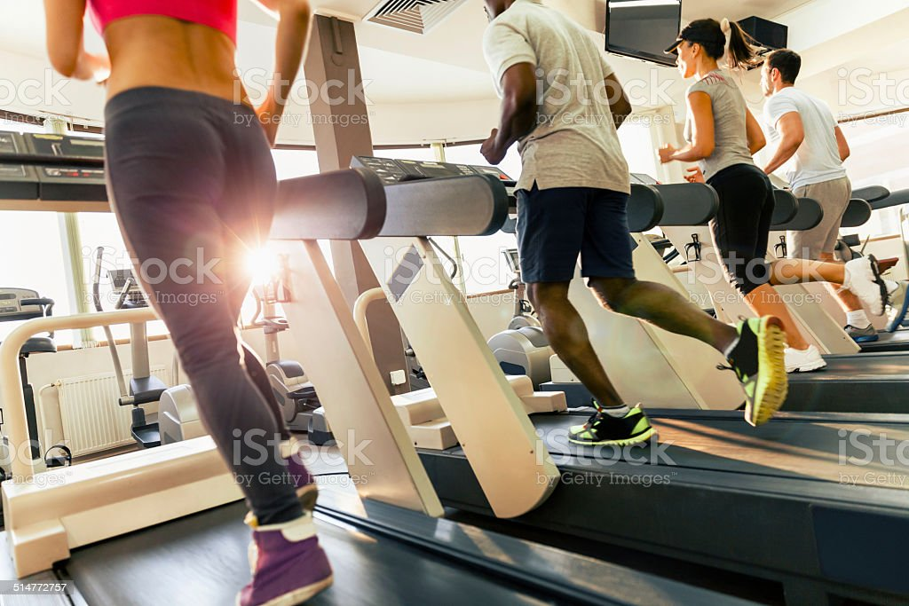 Photo of four young people running on treadmill stock photo