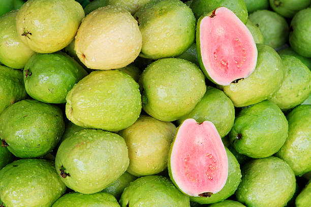 A photo of fresh red guavas, a typical tropical fruit Fresh guavas with pink flesh being sold in a Vietnamese market guava stock pictures, royalty-free photos & images