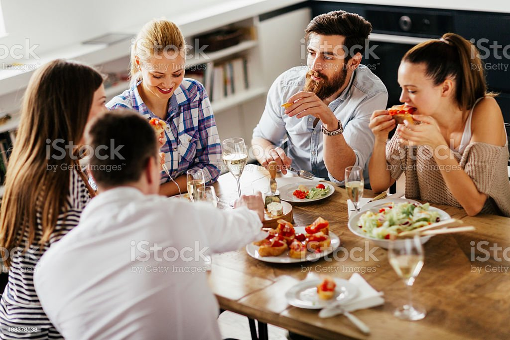 Photo of friends enjoying appetisers and wine at home stock photo