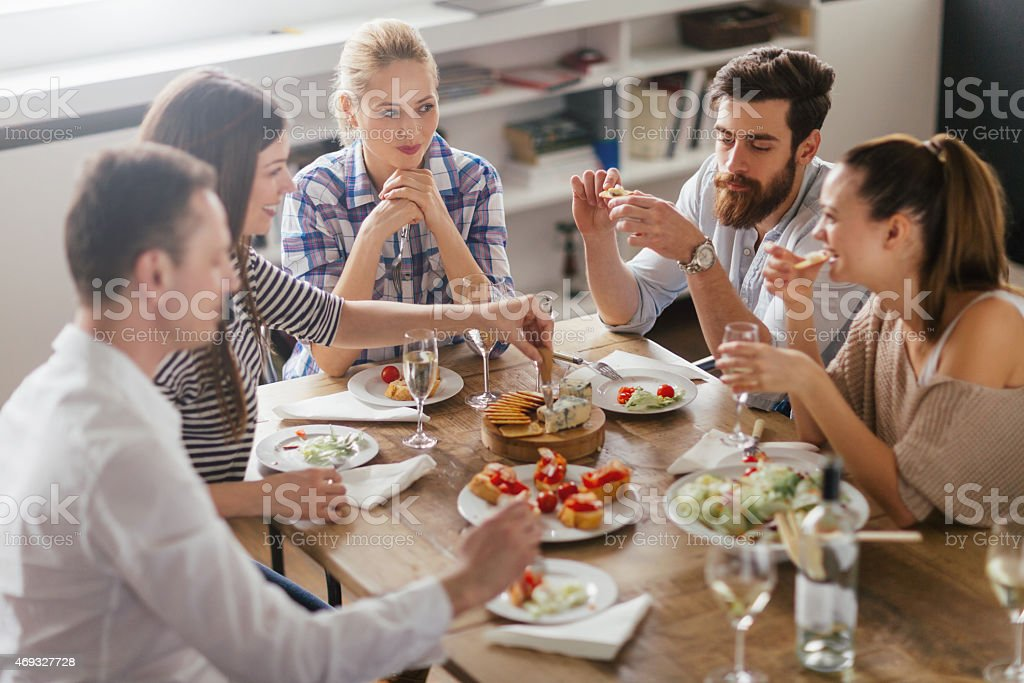 Photo of friends enyoing appetizers and white wine stock photo