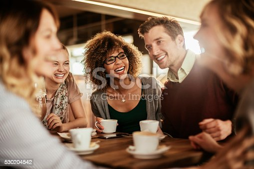 Picture of friends smiling and sitting in a cafe having coffee together.