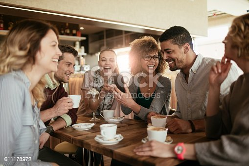 Picture of friends smiling and sitting in a cafe having coffee and using a phone
