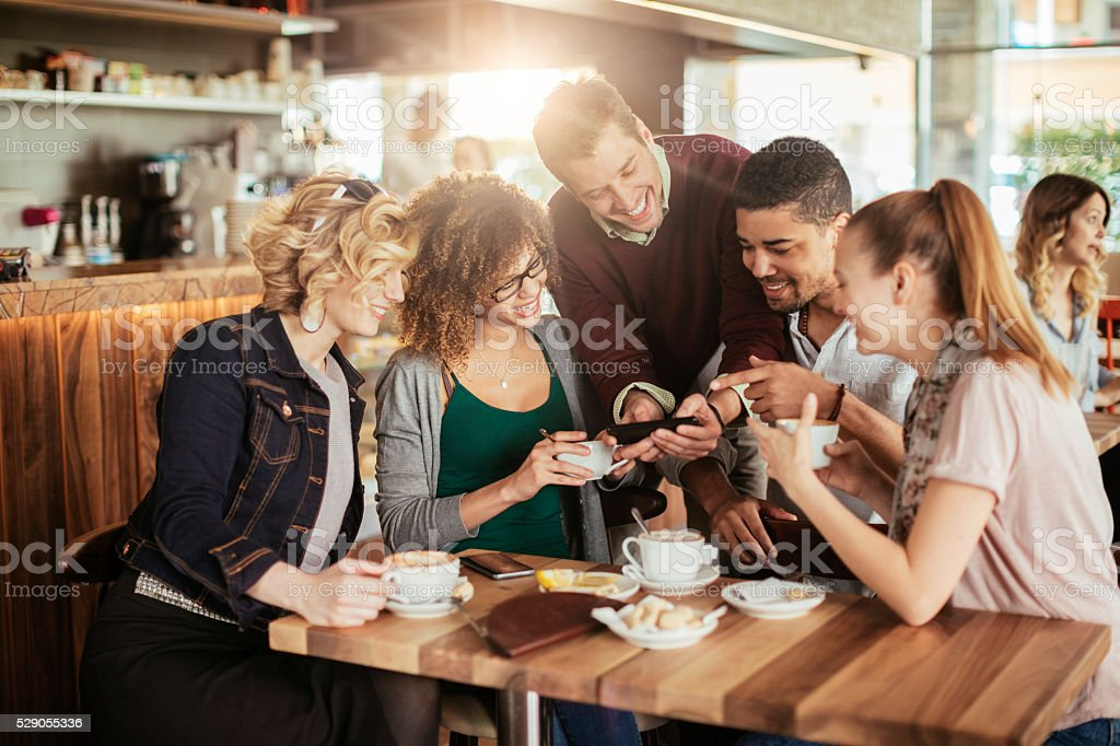 Photo of friends looking at a phone in a cafe stock photo
