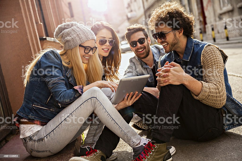 Photo of friends sitting on sidewalk looking at tablet stock photo