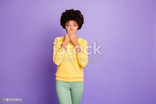 istock Photo of frightened horrified terrified girlfriend covering her mouth with hands after having told restricted private information wearing, green pants trousers yellow sweater trendy stylish isolated over purple pastel color background 1181211014