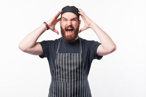 Photo of frustrated bearded chef looking at the camera over white background.