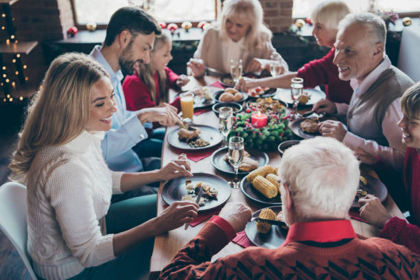 photo of full family gathering sitting around dinner table communicating x-mas party tradition all together son daughter grandma grandpa in noel decorated living room indoors - family gatherings stock pictures, royalty-free photos & images
