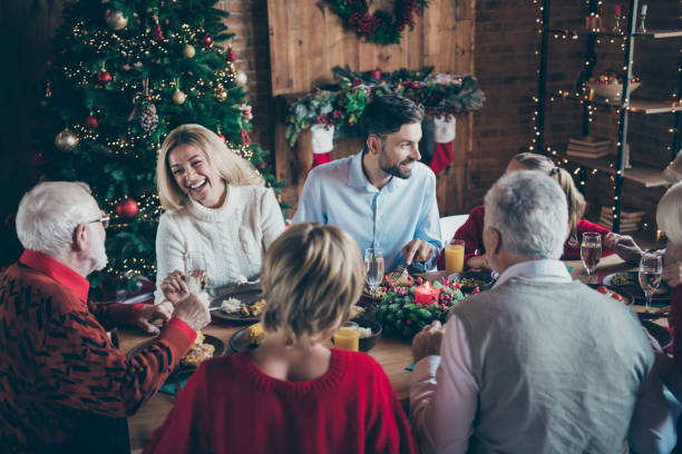 photo of full family gathering sitting dinner table communicating chatting overjoyed x-mas party multi-generation in newyear decorated living room indoors - family christmas imagens e fotografias de stock