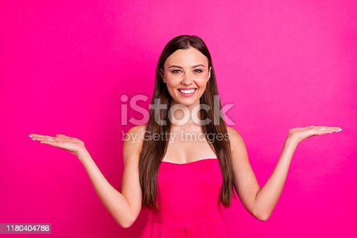 933380808 istock photo Photo of funny lady holding arms empty space presenting new products showing low shopping prices wear bright cute dress isolated vivid pink color background 1180404786