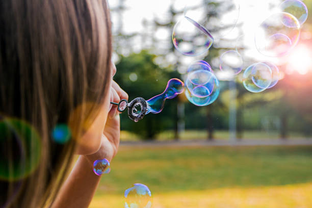 Photo of girl blowing bubble soap outdoor stock photo