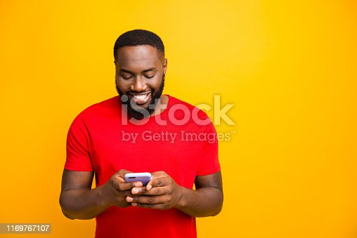 istock Photo of glad cheerful nice cute black man browsing through his phone and chatting to his friend while isolated with yellow background 1169767107