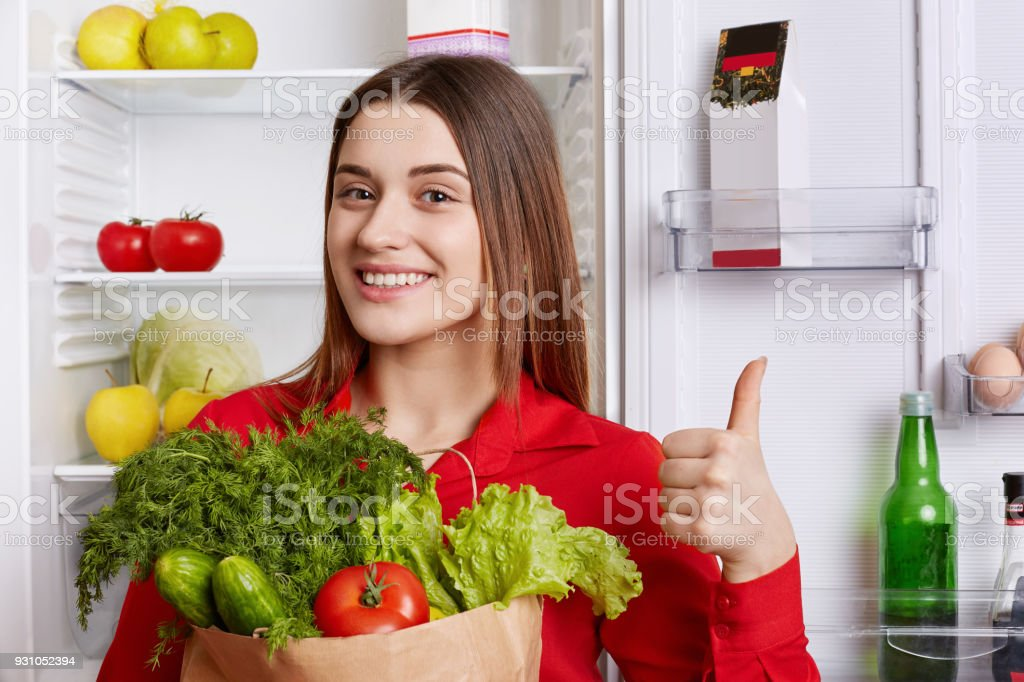 Photo of glad female shows ok sign and demonstrates approval, holds vegetables, comes from grocer`s shop, being in good mood has necessary products for making fresh vegeterian salad poses in kitchen stock photo