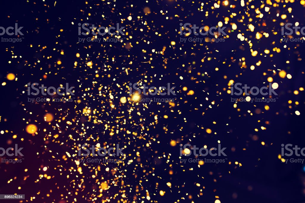 Photo of golden glitter on a black background. Golden explosion stock photo