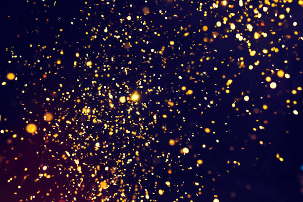 photo of golden glitter on a black background. golden explosion - glamour stock photos and pictures