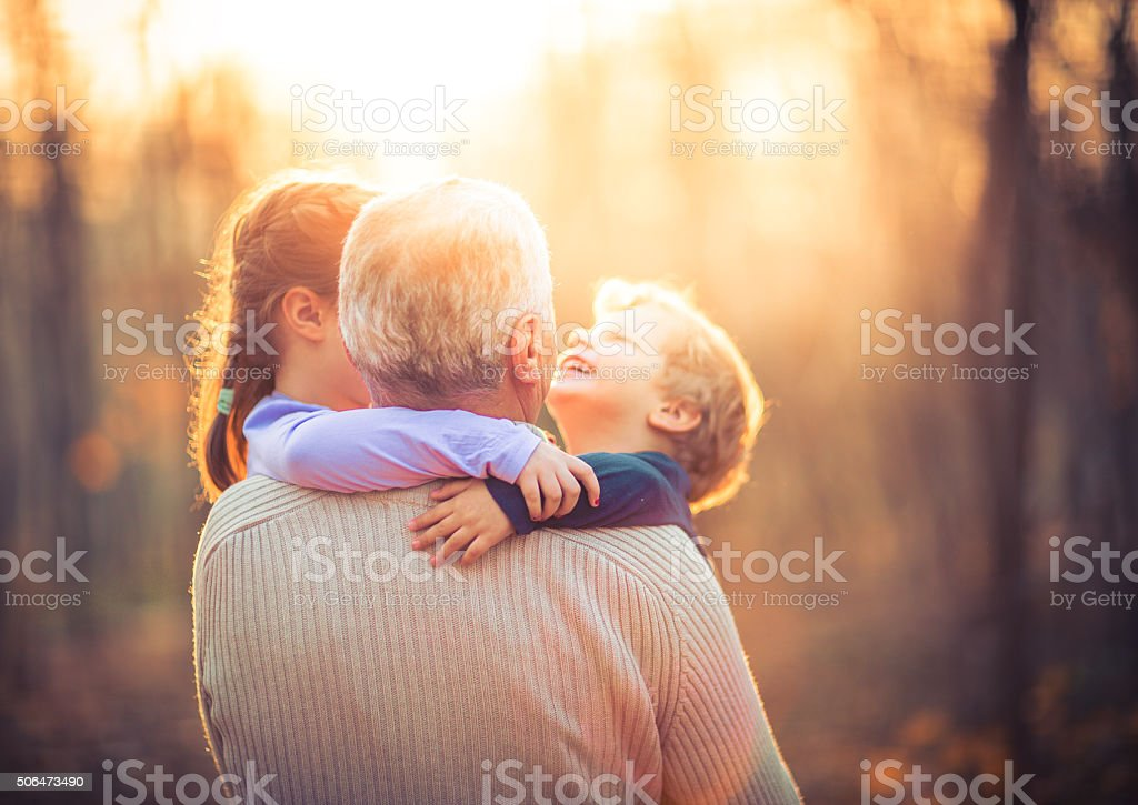 Photo of grandfather and his grandchildren in the park stock photo