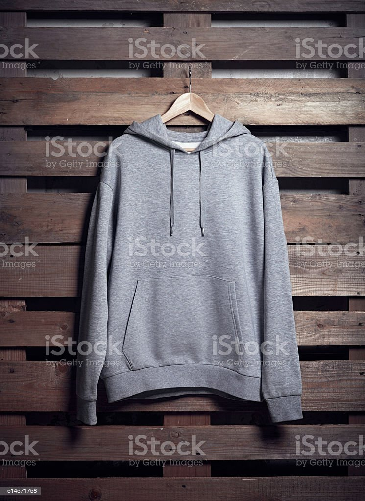 Photo of gray hoody holding on wood background. Vertical blank stock photo