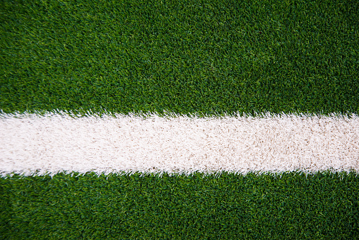Photo of green grass and white line on football stadium.