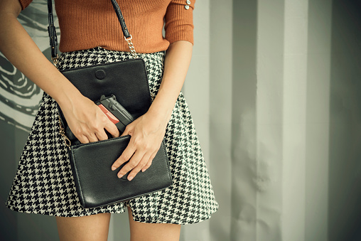 istock Photo of hand of young woman pulling a pistol out of her handbag with free copy space. Self defences concept 963093880