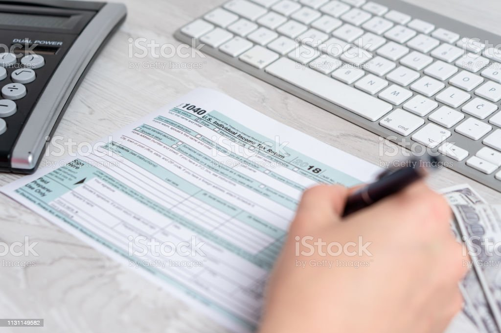 Point of view photo of woman calculating and filling US tax form next...