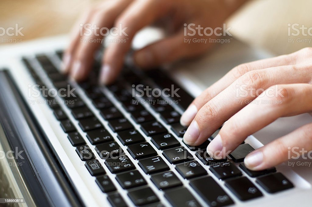 Photo of hands typing text on a laptop keyboard royalty-free stock photo