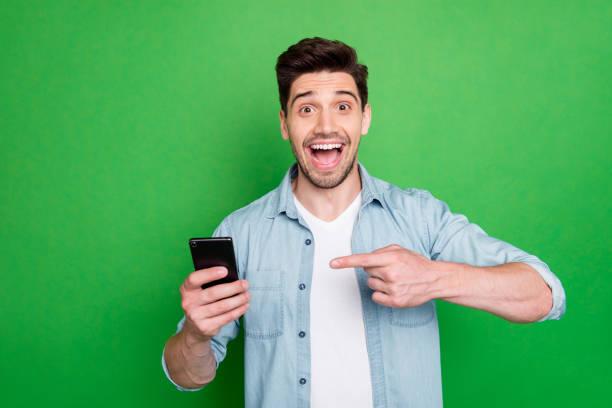 Foto von schönen Kerl hält Telefon Hand zeigt Finger Beratung coolen Preis für Smartphone tragen Jeanshemd isoliert grüne Farbe Hintergrund – Foto