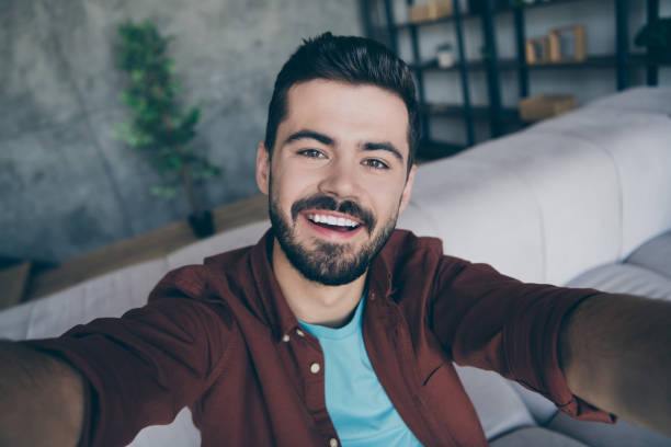 photo of handsome guy in living room enjoy weekend making selfies speaking skype with friends showing new flat modern apartment indoors casual dressed - skype imagens e fotografias de stock