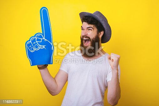 istock Photo of handsomea bearded guy in hat, with big blue fan glove, screaming and celebrating the winning of his favorite team 1163522311