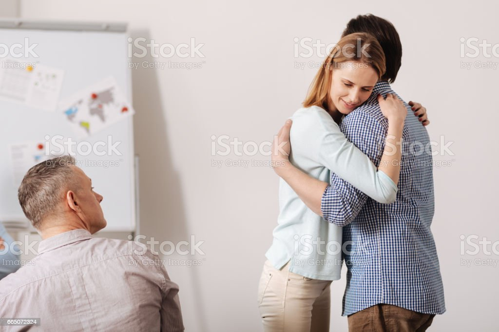 Photo of happy couple embracing at workplace stock photo