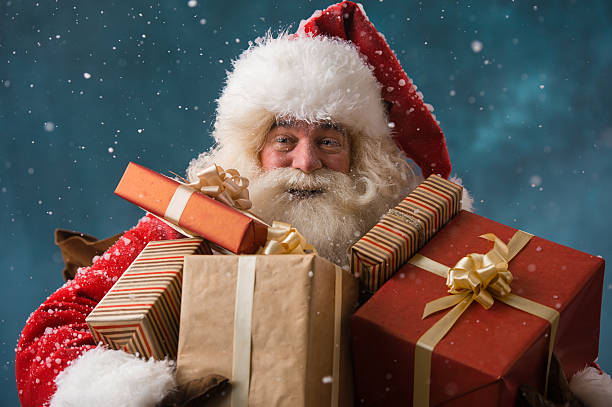 Photo of happy Santa Claus outdoors in snowfall carrying gifts stock photo