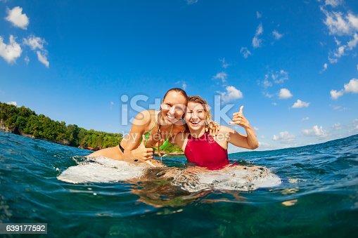 583830686istockphoto Photo of happy surfer girls sitting on surf boards 639177592