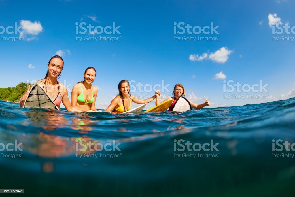Photo of happy surfer girls sitting on surf boards stock photo