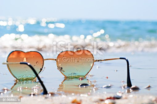 Heart-shaped sunglasses on the wet sand, beach at the seaside. Travel and vacation concept