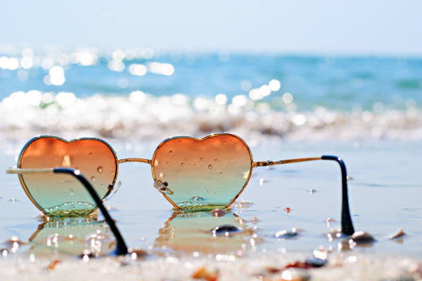 photo of heart-shaped glasses on the beach - summer background стоковые фото и изображения
